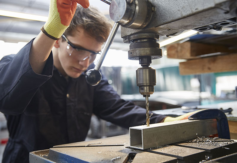 Young apprentice using pillar drill in steel fabrication factory
